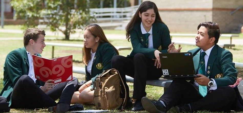 Students sitting in the grounds discussing school work