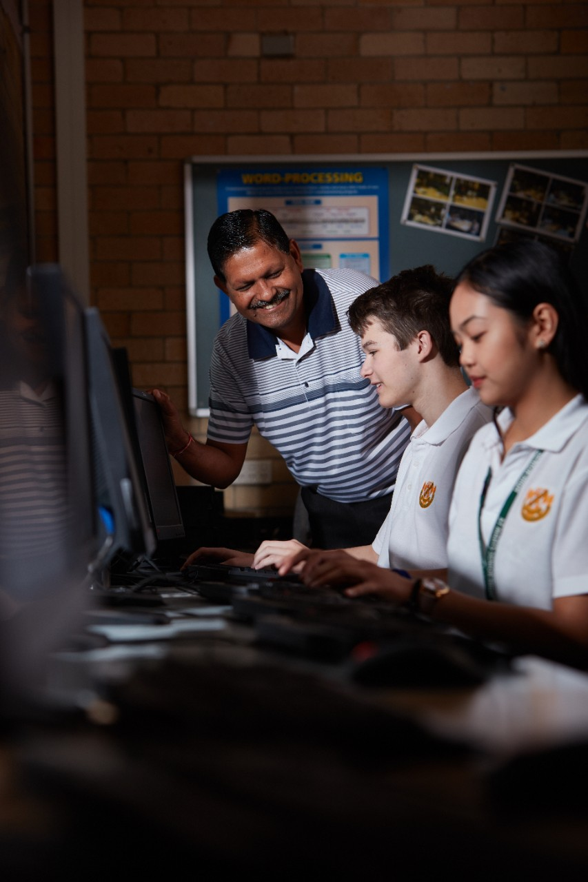 A teacher and two students working on computers